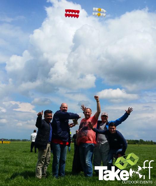 Leuke teamfoto met de vlieger in de lucht.