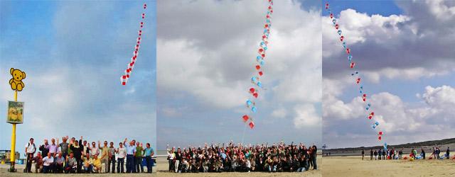 Groepen mensen op het strand met daarboven hun zelfgemaakte vliegertrein in de lucht.