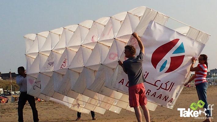 Een Megavlieger wordt door vier mensen vastgehouden voor het oplaten op het strand in Zandvoort.