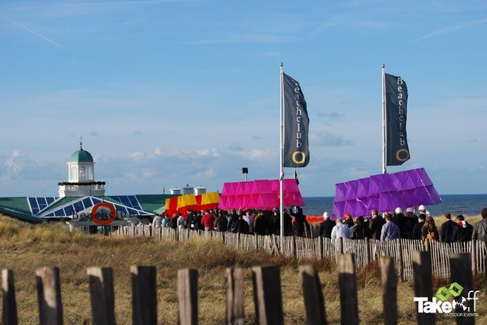Vijf grote Megavliegers worden naar het strand gedragen.