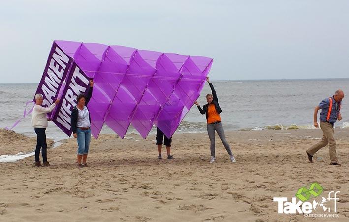 Een zelfgebouwde Megavlieger wordt vastgehouden op het strand zodat we deze kunnen oplaten.