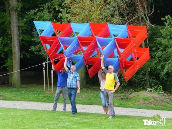 Een hele grote vlieger wordt in een park in Arnhem vastgehouden door vier mensen