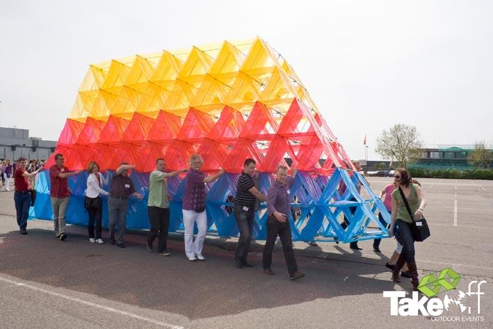Een hele grote Megavlieger in drie kleuren wordt door 18 personen over de parkeerplaats gedragen. Ze lopen naar de plaats waar we de vlieger op gaan laten.