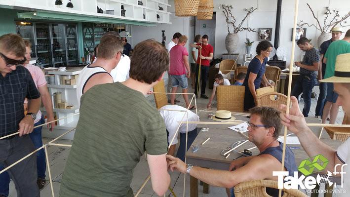 Mensen zijn bezig om een Reuzevlieger te bouwen bij een strandpaviljoen.