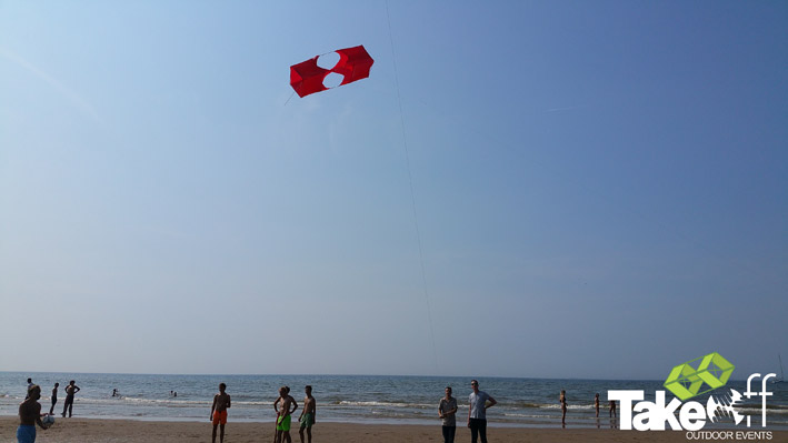 Een grote rode vlieger boven de vloedlijn op het strand in Scheveningen.