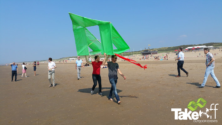 Twee mensen lopen met een enorme vlieger over het strand.