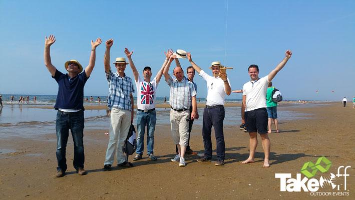 Enthousiaste mensen op het strand die net hun vlieger op hebben gelaten.