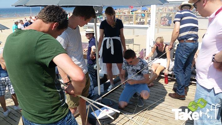 Een groep mensen bouwt samen een vlieger op het terras.