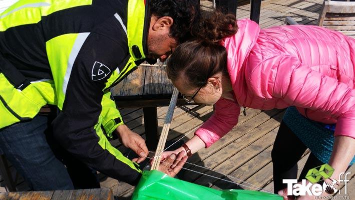 Twee mensen helpen elkaar tijdens het bouwen van hun teamvlieger. Samenwerken is belangrijk.