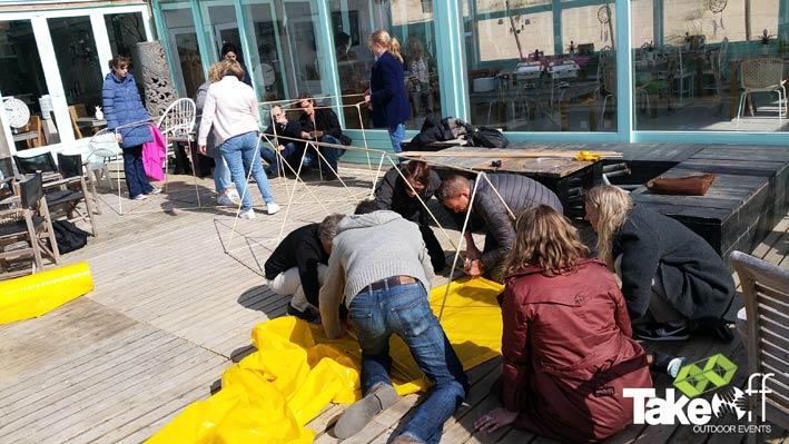 Een groep mensen werkt samen op een terras aan een hele grote reuzevlieger.