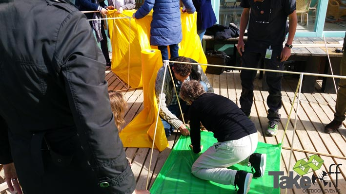 Verschillende teams zijn op een terras aan het bouwen aan hun eigen Reuzevlieger.