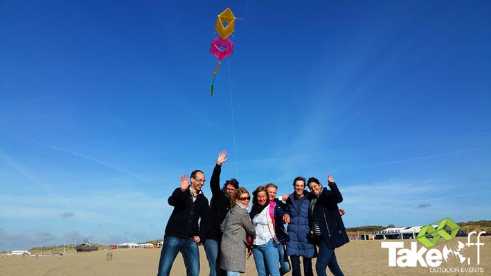 Trotse deelnemers van de workshop Reuzevlieger bouwen op het strand met daarboven hun zelfgemaakte vlieger in de lucht.