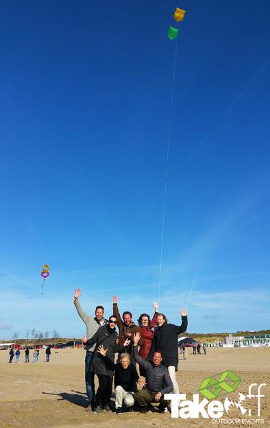Teamfoto van een groepje bouwers met daarboven hun zelfgemaakte reuzevlieger in de lucht.