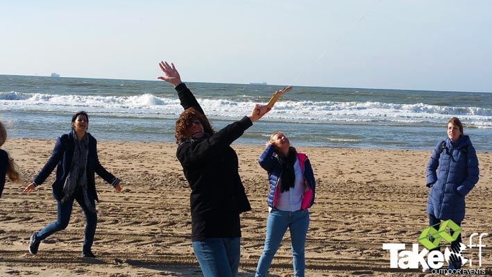 Blije mensen op het strand van Scheveningen die hun vlieger oplaten.