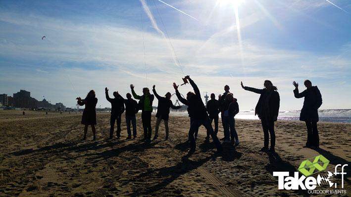 Mensen die op het strand aan het vliegeren zijn met de Pier van Scheveningen op de achtergrond.