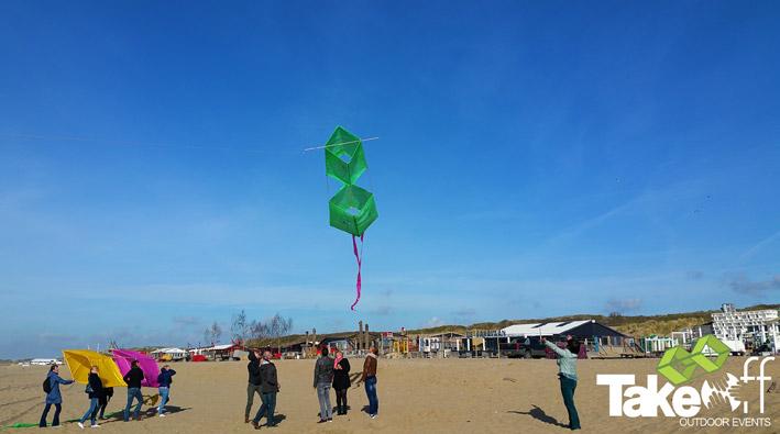 Een Reuzevlieger wordt door een groep mensen de lucht in geholpen op het strand.