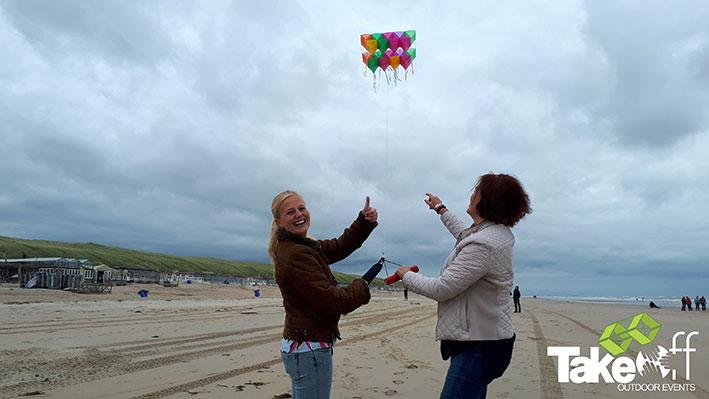 De Megavlieger hangt hier mooi in de lucht boven het strand met twee deelnemers op de voorgrond.